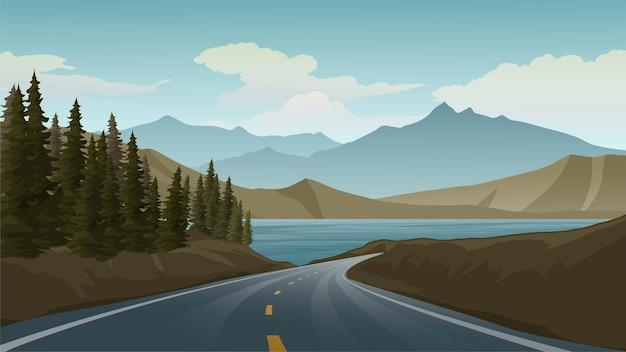 Strada vuota in montagna con lago e pini