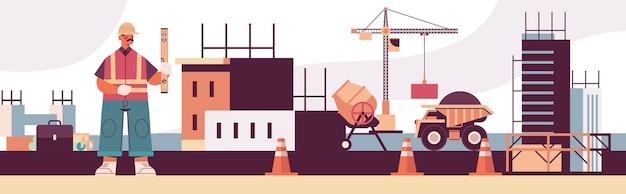 Ingegnere in uniforme tenendo la costruzione a livello di edifici concept builder in casco e gilet lavorando sul cantiere