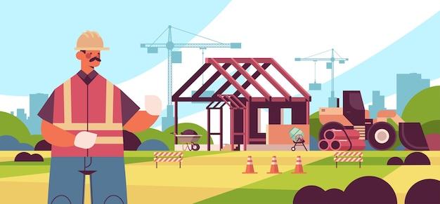 Ingegnere in uniforme supervisione processo costruzione edifici concept builder in casco e gilet lavorando sul ritratto del cantiere