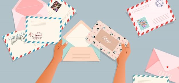 Buste e cartoline sul tavolo. mani in possesso di una busta. vista dall'alto verso il basso. biglietto di auguri e una lettera in una mano. illustrazione moderna per il web e la stampa. retro carte e buste.