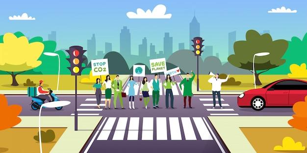 Attivisti ambientali sul bivio tenendo manifesti andare verde salva pianeta concetto manifestanti campagna per proteggere la terra dimostrando contro il riscaldamento globale paesaggio urbano a figura intera orizzontale