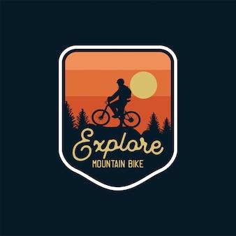 Esplora mountain bike distintivo silhouette tramonto sullo sfondo. toppa con logo