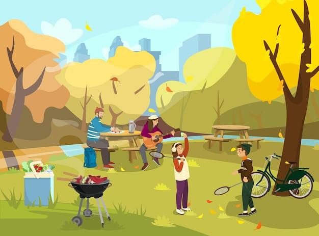 Famiglia che fa picnic nel parco autunnale bambini che giocano a badminton