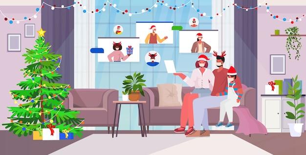 Famiglia in maschere discutendo con amici di razza mista durante la videochiamata coronavirus quarantena concetto di autoisolamento capodanno vacanze di natale celebrazione soggiorno interno