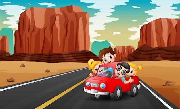 Famiglia che viaggia in macchina rossa attraverso il deserto