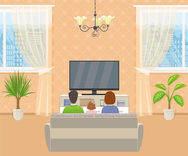 Famiglia che guarda la tv nell'interno del soggiorno. padre, madre e bambina si rilassano sul divano.