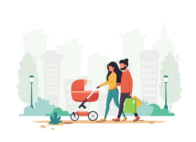 Famiglia con carrozzina che cammina nel parco.