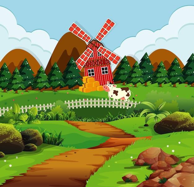 Fattoria nella scena della natura con mulino a vento e mucca
