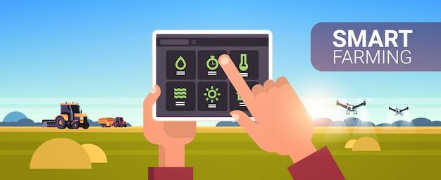 Mani di agricoltore utilizzando tablet controllo trattore e drone spruzzatore sul campo intelligente agricoltura moderna tecnologia organizzazione della raccolta concetto di applicazione paesaggio sfondo orizzontale spazio di copia