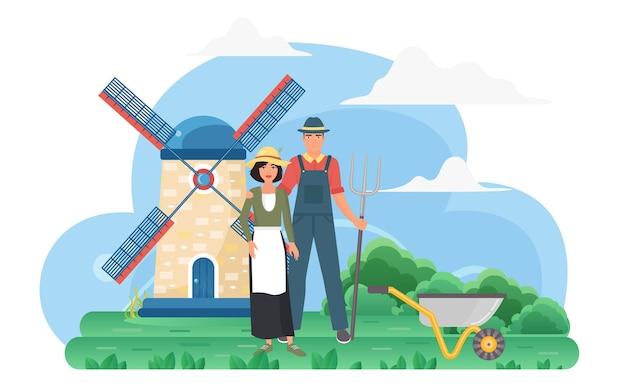 Contadino nel paesaggio rurale del villaggio ecologico con i lavoratori agricoli del mulino a vento in piedi