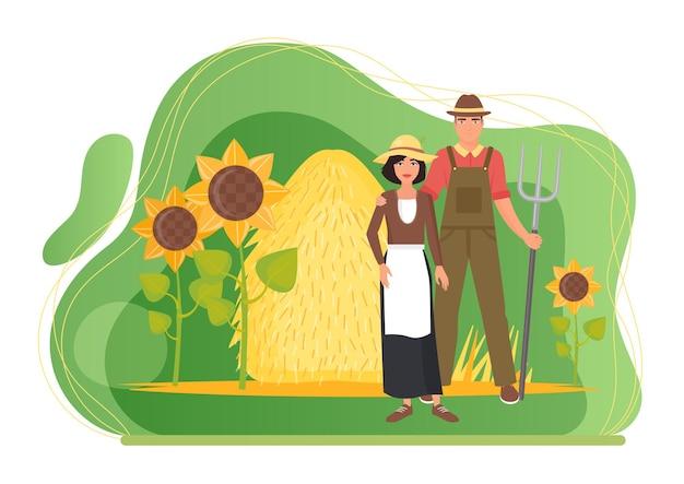 Gli agricoltori coppia persone in piedi nel paesaggio del villaggio di fattoria con pagliaio e girasoli