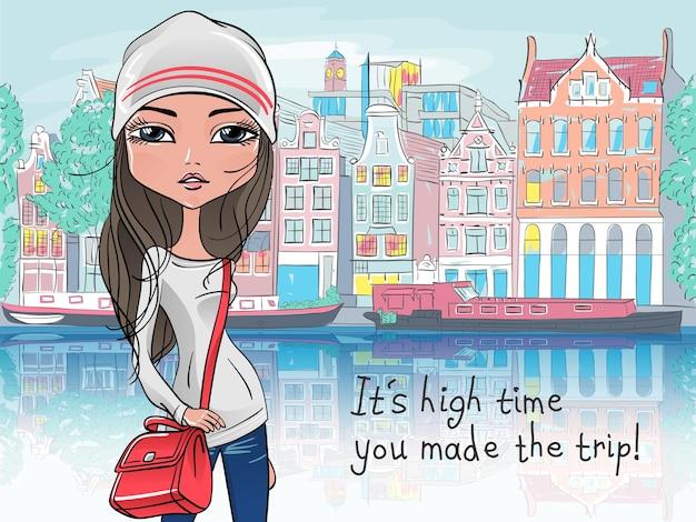 Turista della ragazza alla moda hipster in una giacca di pelle, jeans e stivali rossi che cammina per strada ad amsterdam con la tradizionale casa olandese