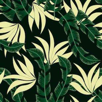 Modello tropicale senza cuciture alla moda con piante luminose e foglie su un nero.