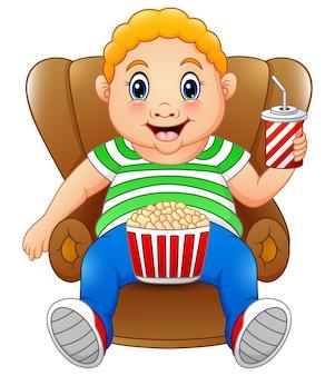 Uomo grasso seduto sulla sedia con popcorn e bere