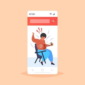Uomo grasso versare il caffè sulla camicia sovrappeso uomo afroamericano con macchia sui suoi vestiti seduto sulla sedia disordine concetto di obesità smartphone schermo app mobile online