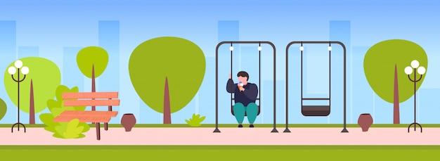 Grasso ragazzo obeso oscillante e mangiare il gelato malsano nutrizione concetto di obesità sovrappeso uomo seduto sull'altalena divertendosi parco estivo all'aperto paesaggio