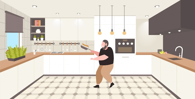 Grasso uomo obeso cucinare frittelle in padella malsana nutrizione concetto di obesità sovrappeso ragazzo preparazione colazione moderna cucina interna