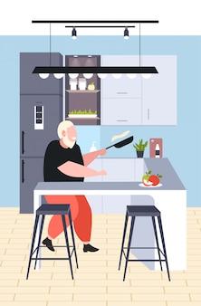 Grasso uomo obeso cottura frittelle in padella malsana nutrizione concetto di obesità sovrappeso ragazzo preparazione colazione seduto al banco scrivania moderna cucina interno verticale