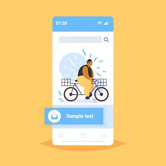 Grasso uomo obeso in sella a bici sovrappeso ragazzo afro-americano in bicicletta bicicletta perdita di peso concetto smartphone schermo applicazione mobile online