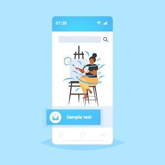 Grasso donna obesa pittore utilizzando pennello e tavolozza sovrappeso ragazza afroamericana artista pittura su cavalletto occupazione creativa concetto di obesità smartphone schermo mobile app online