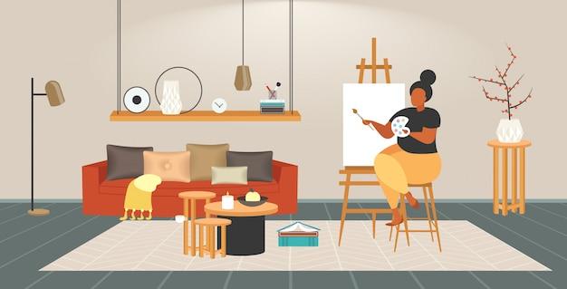 Pittore grasso donna obesa con pennello e tavolozza sovrappeso ragazza artista pittura su cavalletto occupazione creativa concetto di obesità interno moderno salotto