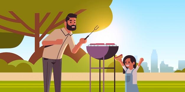 Padre e figlia che preparano hot dog sulla famiglia felice della griglia divertendosi orizzontale piano del ritratto del fondo di paesaggio del parco di estate di concetto del partito del barbecue di picnic