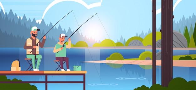 Padre e figlio pesca insieme dal molo uomo con ragazzino utilizzando canne famiglia felice fine settimana pescatore hobby concetto acqua orizzonte foresta paesaggio sfondo piatto lunghezza orizzontale