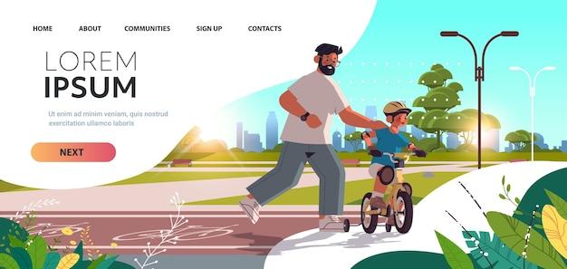 Padre che insegna al figlio piccolo ad andare in bicicletta nel parco urbano genitorialità paternità concetto papà trascorrere del tempo con il bambino paesaggio urbano sfondo orizzontale a figura intera copia spazio illustrazione vettoriale