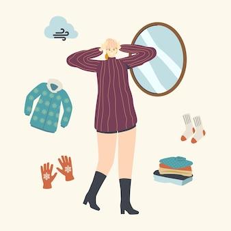 Personaggio femminile in abiti caldi alla moda prova il cappello lavorato a maglia davanti allo specchio per camminare all'aperto