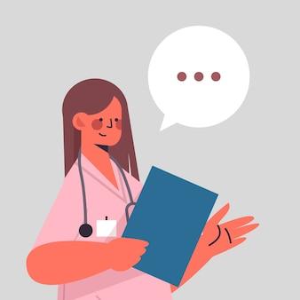 Dottoressa in uniforme holding appunti chat bolla comunicazione sanità medicina concetto donna operaio medico ritratto