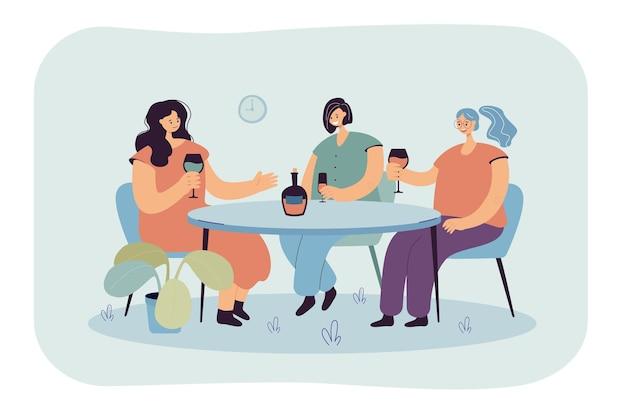 Amici femminili che si siedono al tavolo in caffè e bere vino