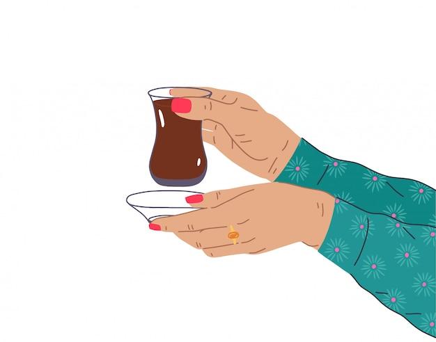 Una mano femminile con una bella manicure e gioielli tiene una tazza di tè turco. illustrazione