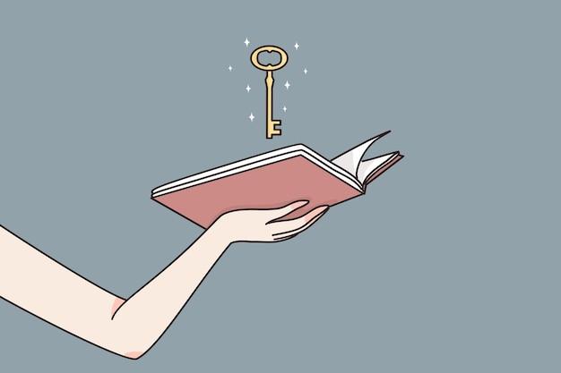 Mani femminili che tengono il libro aperto con la chiave d'oro magica che significa possibilità di sbloccare la saggezza