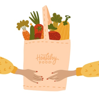 Mani umane femminili che tengono eco borsa piena di verdure isolate su sfondo bianco ecofriendly shopp...