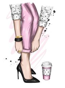 Piedini femminili in scarpe e pantaloni alla moda e un bicchiere di caffè