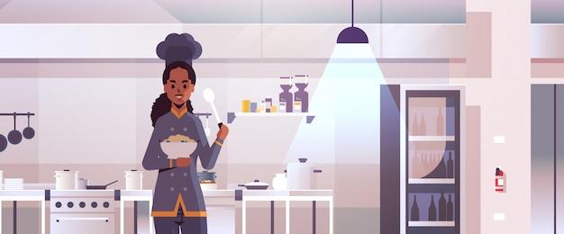Piatto professionale femminile della tenuta del cuoco del cuoco unico con porridge e cucchiaio donna afroamericana nel piatto uniforme dell'assaggio che cucina ritratto moderno dell'interno del ristorante della cucina di concetto dell'alimento