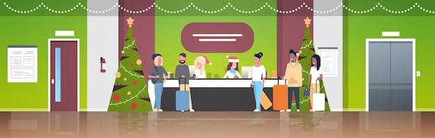 Receptionist femminili in cappelli di babbo natale che incontrano i turisti con i bagagli al banco della reception registrazione concetto di vacanza di natale interni moderni hall dell'hotel