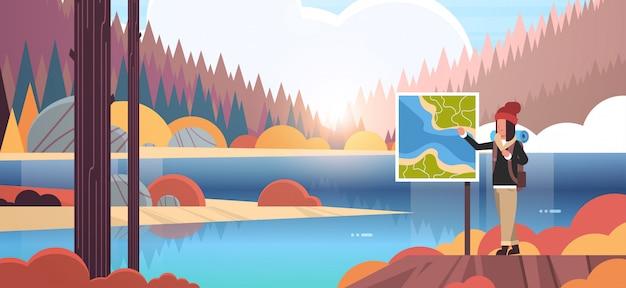 Viandante turistica femminile con lo zaino che guarda la mappa di viaggio del viaggiatore che pianifica itinerario di viaggio che fa un'escursione concetto montagne di foresta del fiume della natura del paesaggio di alba di autunno