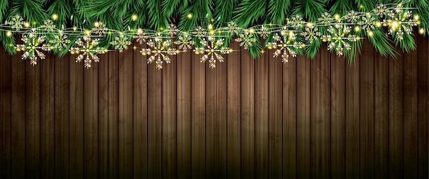 Ramo di abete con luci al neon e ghirlanda dorata con fiocchi di neve su struttura in legno
