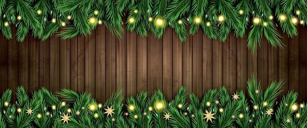 Ramo di abete con luci al neon e stelle dorate su fondo in legno. buon natale e felice anno nuovo.