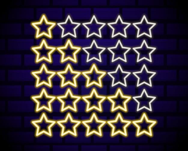 Cinque stelle al neon gialle valutazione elemento di design isolato sul muro di mattoni scuri.