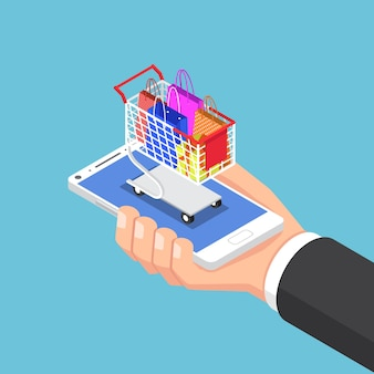 Mano isometrica piana dell'uomo d'affari 3d con la borsa della spesa e carrello sullo smartphone. concetto di acquisto online.