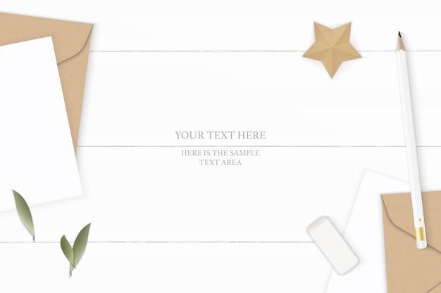 Piatto laici vista dall'alto elegante composizione bianca lettera carta kraft busta foglia gomma da cancellare e mestiere a forma di stella su sfondo di legno.