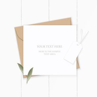 Piatto laici vista dall'alto elegante composizione bianca lettera kraft busta di carta natura foglia e tag su sfondo di legno.