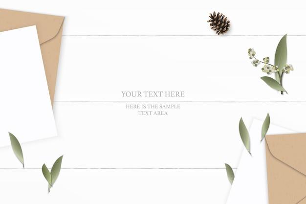 Piatto laici vista dall'alto elegante composizione bianca lettera carta kraft busta pigna fiore foglia su sfondo di legno.