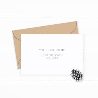 Flat top view elegante composizione bianca lettera kraft busta di carta cono di pino su sfondo di legno.