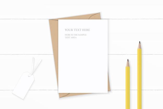 Piatto laici vista dall'alto elegante composizione bianca lettera carta kraft busta matite gialle e tag su sfondo di legno.