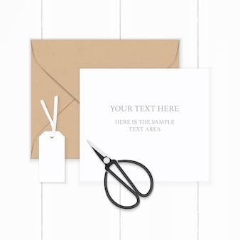 Piatto laici vista dall'alto elegante composizione bianca carta kraft marrone etichetta della busta e forbici vintage in metallo su fondo in legno