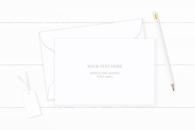 Piatto laici vista dall'alto elegante composizione bianca carta busta matita tag su sfondo di legno.