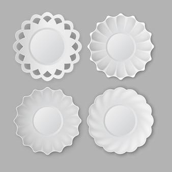 Quattro piatti rotondi d'epoca in ceramica bianca vuota su sfondo grigio